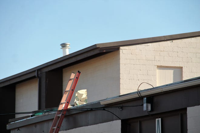 A ladder leans against one of the Alamogordo Public Schools Administration buildingsnext to a piece of the damaged roof September 17, 2021.  Roof damage was reported following an overnight wind storm occuring September 16-17, 2021.