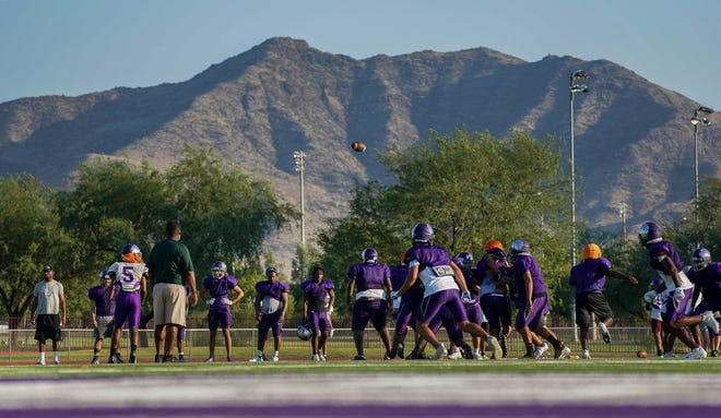 Cesar Chavez players practice in front of South Mountain during a practice at Cesar Chavez High School Sept, 15, 2021. The school is part of the Phoenix Union High School District.