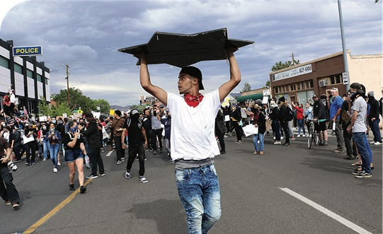 Photographer Jason Bean won Photo of the Year in the Nevada Press Association contest for his photo of a man carrying a shield ripped from the Reno Police Department headquarters during unrest that broke out after a Black Lives Matter rally on May 30, 2020.