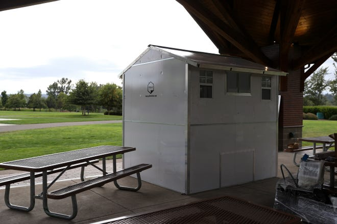 People view prefabricated transitional homes for houseless or unsheltered individuals at a pallet shelters sponsor event in Salem, Ore. on Friday, Sept. 17, 2021. Both units cost $5,000 to sponsor.