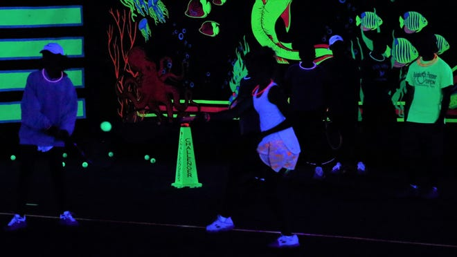 A player hits a forehand during the XGLOsive Tennis event at Bentwood Country Club on Thursday, Sept. 16, 2021. The glow-in-the-dark spectacular featured backlights, flourescent graphics and upbeat music.
