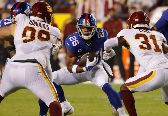 New York Giants running back Saquon Barkley (26) carries the ball as Washington Football Team defensive tackle Matt Ioannidis (98) and safety Kamren Curl (31) chase.
