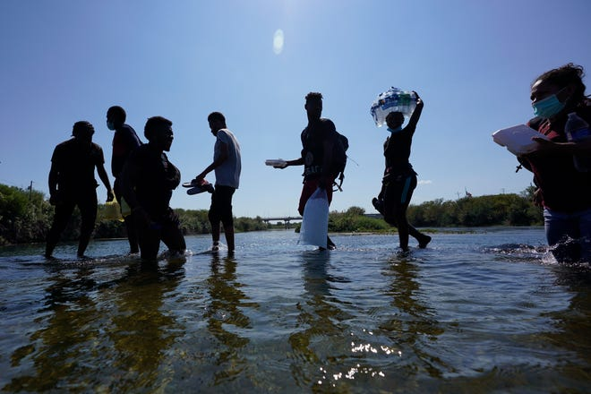 Haitian migrants use a dam to travel from Mexico to the United States in Del Rio, Texas, Friday, September 17, 2021.