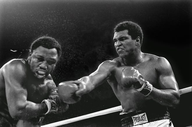ORG XMIT: NY155 FILE - In this Oct. 1, 1975 file photo, spray flies from the head of challenger Joe Frazier, left, as heavyweight champion Muhammad Ali connects with a right in the ninth round of their title fight in Manila, Philippines.(AP Photo/Mitsunori Chigita, File)