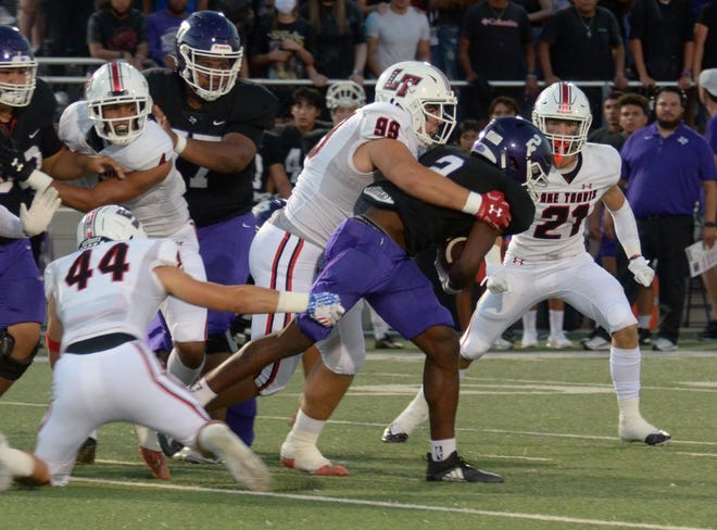 Lake Travis defensive tackle Griffen Willis wraps up San Marcos running back Jaidyn Brown early in Friday's District 26-6A game as teammates Lucas Roland, left, and Max Swanson close in on the play. Lake Travis topped San Marcos 45-6.