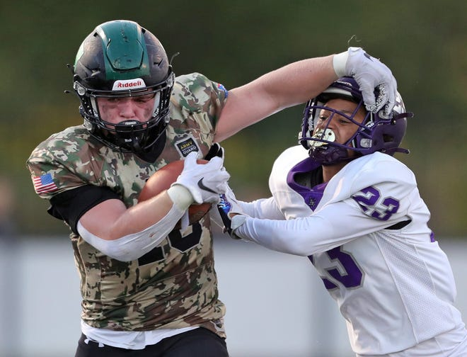 Highland running back Lukas Stiles, left, stiff-arms Barberton defensive back Kenneth Larry during the Magics' 28-21 win Friday night in Medina. [Jeff Lange/Beacon Journal]