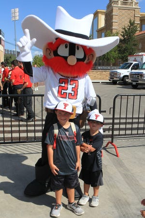 The Texas Tech Red Raiders mascot poses with young fans outside Jones AT&T Stadium before the game against the Florida International Panthers.