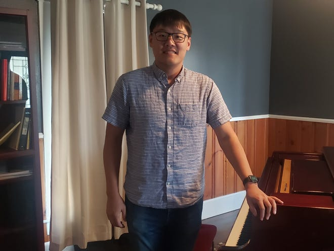 Minwoo Park stands beside the practice piano in the recently opened Ardmore Piano Studio. Park, who is currently working on a doctorate in piano performance, will offer piano lessons as well as lessons in his native Korean language.
