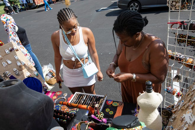 """Nyasia Crandall, left, looks for jewelry with help from Astrid Coffi, owner of Coffi Co. African Beauty and Fashion, during the Columbus African Festival at Franklin Park in Columbus Saturday. """"I thought the jewelry was really nice,"""" Crandall said. """"I grabbed some for me and my boo."""""""