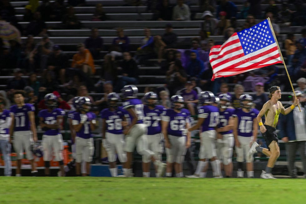 A Columbia Central High School fan rushes along the field carrying the American flag before a victory 30-7 game against Nolensville at Lindsey Nelson Stadium in Columbia, Tenn., on Friday, Sept. 17, 2021.