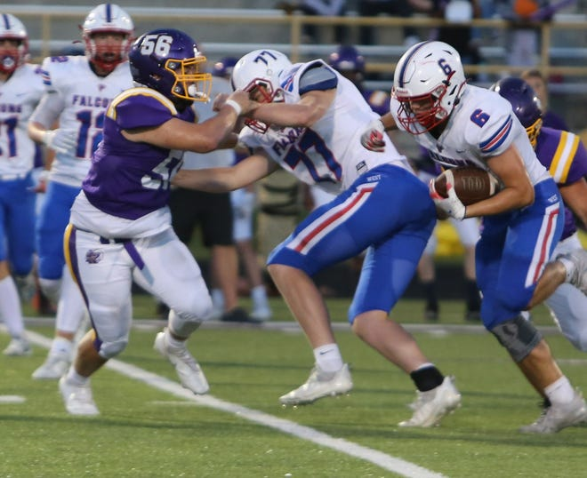 North Henderson defender Dylan Blackwell (56) gets ready to tackle West Henderson running back Andrew Schultz (6) during Friday's game as Connor Brittian (77) blocks.