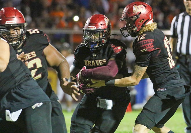 Lake Gibson running back Jaylon Glover takes the handoff from quarterback Logan Hackett and looks for a hole against Lakeland.