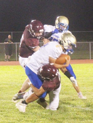 Swink High School's Clay Roweth (5) and Ben Miner (3) tackle Dolores Huerta's Alejandro Lopez in a game on Sept. 17 at Gene Brown Field. The Lions defeated the Scorpions 34-12.
