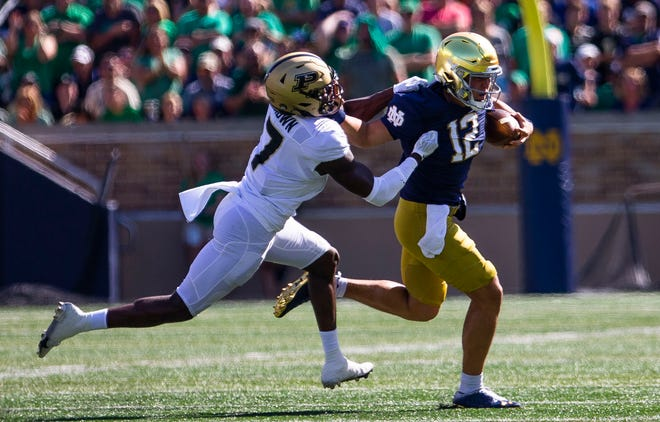 Notre Dame QB Tyler Buchner (12) gets away from Purdue's Jamari Brown (7) during ND's 27-13 win over Purdue, Saturday, Sept. 18, 2021, at Notre Dame Stadium.