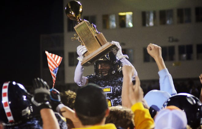 Gaylord's Gavin Freeman is hoisted up with the Jaycees Traveling Trophy after the Blue Devils' 10-7 victory over Petoskey Friday night, which ended a streak of three-straight wins by the Northmen in the series.