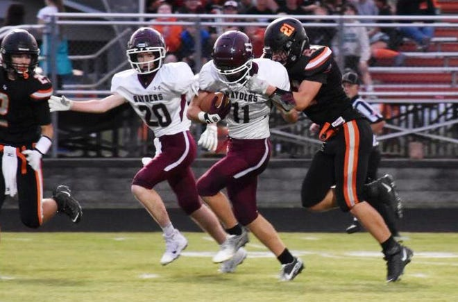 Charlevoix's Max Dixon (11) drags an Elk Rapids player down the field during Friday's game on the road.