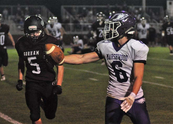 Marshwood's Ty Cougler, right, extends the football towards the end zone as he scores one of his two touchdowns during Friday night's 48-21 Class B win in Gorham, Maine. Giving chase is Gorham's Elijah Wyatt.