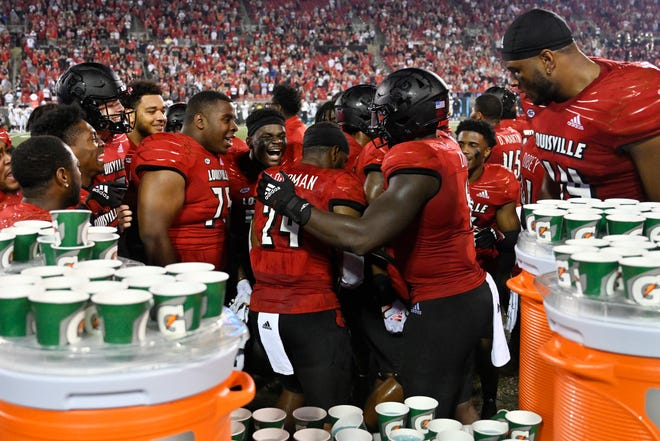 Louisville linebacker Jaylin Alderman (24) is surrounded by his celebrating teammates after he intercepted a pass and returned it for a touchdown against UCF with 13 seconds remaining to give the Cardinals a 42-35 victory Friday night.