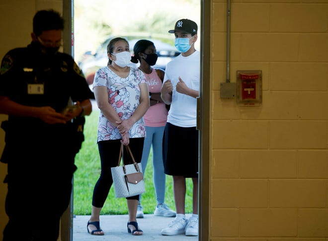 People line up Saturday for COVID-19 shots during a vaccination event at the at the Ezell Hester Jr. Community Center in Boynton Beach. The city  gave $100 gift cards to the first 500 people who received a shot. MEGHAN McCARTHY/The Palm Beach Post