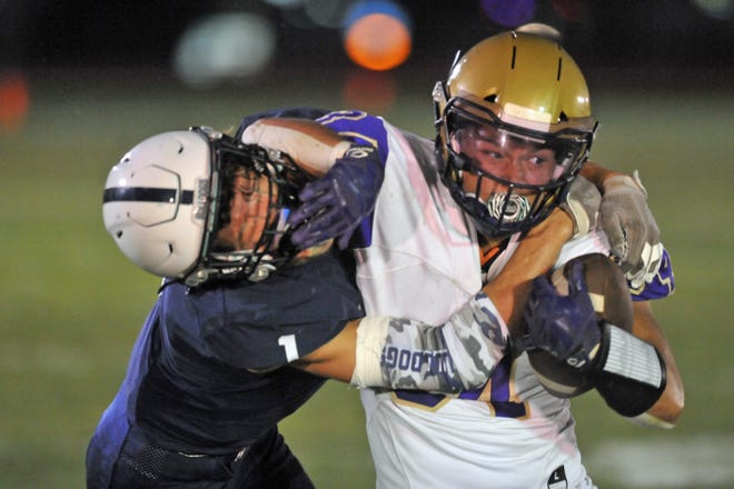 St. Raphael running back Napoleon DeBarros, right, tries to shake loose from a tackle by Westerly's Luke Marley during the first quarter of Friday's Division II matchup.