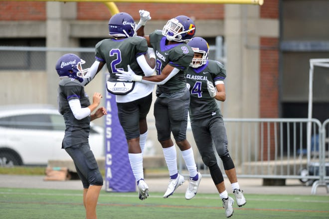 Classical's Elijah Nyakhoon (9) celebrates with Jordan Duke (2) and other teammates after his 51-yard touchdown catch in the first quarter of the Purple's win over Mt. Hope on Friday.