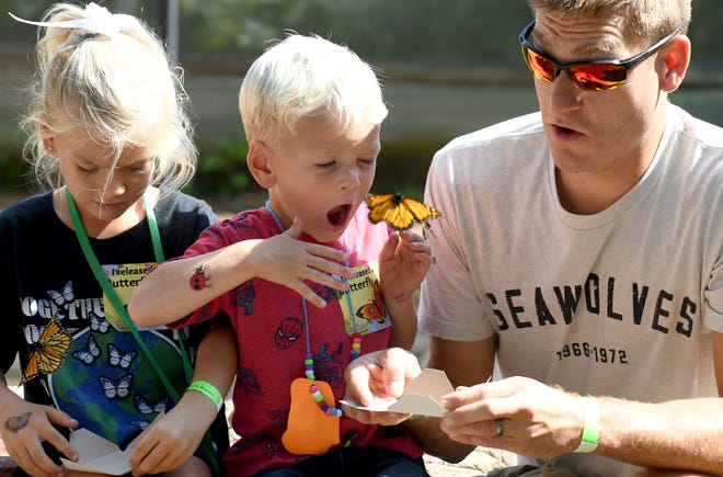Lacey, 5, and Kai Woods, 3, with their father Justin Woods of Plain Township release a butterfly at Beech Creek Botanical Garden and Nature Preserve during Saturday's butterfly release celebration.