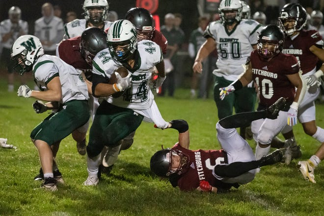 Despite a defender grabbing onto his shirt, Wachusett Regional running back Angelo Smith runs to a first down against Fitchburg.