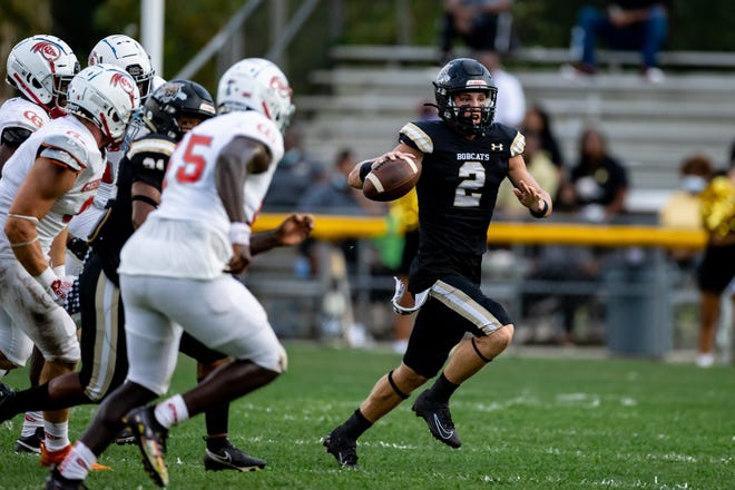 Buchholz quarterback Creed Whittemore runs away from Cardinal Gibbons defenders during the first quarter Friday at Citizens Field.