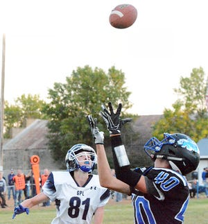 Florence-Henry's Clay Trupe (40) hauls in a long pass against Great Plains Lutheran defender Alex Heil during their high school football game Friday night in Florence. The Falcons (5-0), who celebrated homecoming with a 47-0 win, have moved up to No. 3 in this week's state Class 9AA rankings.