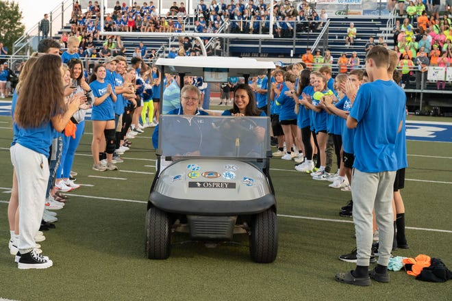 On Friday, Harper Creek renamed its ticket booths at the football field in honor of Norma Krutsch and Linda Irish. Here, Krutsch is escorted on to the field by Harper Creek athletic secretary Melissa Feasel.