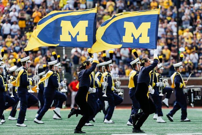 A equipe do Michigan entra em uma manifestação antes do jogo do Northern Illinois, no Michigan Stadium, em Ann Arbor, no sábado, 18 de setembro de 2021.
