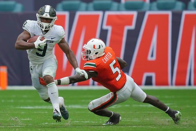 Os espartanos do estado de Michigan acertam Kenneth Walker III com a bola que ultrapassou a segurança do furacão Amari Carter de Miami durante o segundo tempo em Miami Gardens, Flórida, em 18 de setembro de 2021.