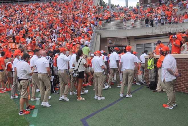 Officials move players  and fans out of the field and stands with 32 seconds left in the second quarter with  a lightning delay in the Clemson, S.C., September 18, 2021.