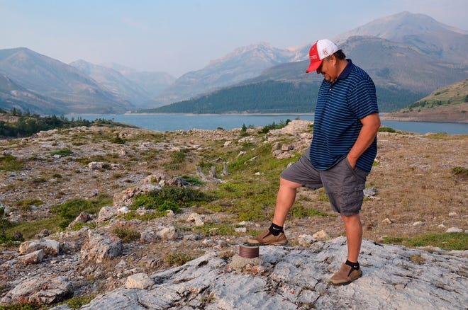 FILE - In this July 2021 file photo, with the peaks of the Badger-Two Medicine rising behind him Keith Tatsey toes a Bureau of Reclamation boundary marker indicating the edge of the Blackfeet Indian Reservation. Tasty and his brother, Terry Tatsey, spent a week in July with friends and family in the area to swap stores of hunting trips, took children on horseback rides and watched traditional dances and played traditional games. (Rob Chaney/The Missoulian via AP, File)