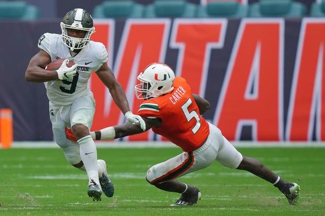 Sep 18, 2021; Miami Gardens, Florida, USA; Michigan State Spartans running back Kenneth Walker III (9) runs the ball past Miami Hurricanes safety Amari Carter (5) during the second half at Hard Rock Stadium.
