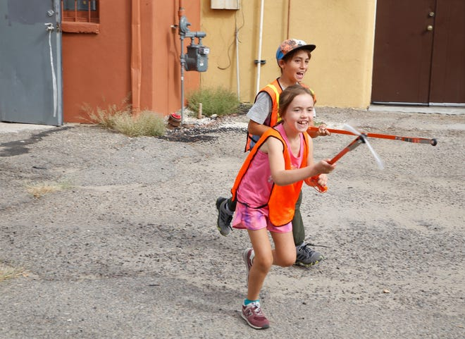 Aurora Unsicker, left, and Henry Unsicker have some fun while picking up litter in downtown Farmington on Sept. 18 as part of the city's participation in World Cleanup Day.