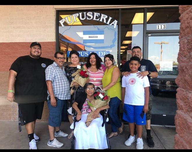 Yesenia Ramírez (center), owner of El Salvadoreño restaurant in Phoenix, with her family in front of her restaurant.