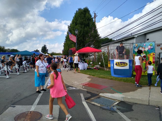 The 44th annual Hang Around Victor Day festival featured several new attractions, including a dunk tank sponsored by the Chamber of Commerce (right) and an outdoor spin cycle class from Spoke Cycle and Row Studio (left).