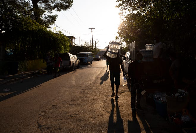 A Haitian migrants carries water back towards the Rio Grande in Ciudad Acuna as migrants buy water and food to carry back into a camp on the U.S. side in Del Rio, Texas.
