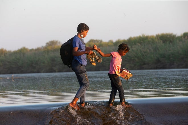 Haitian migrants cross the Rio Grande into Del Rio, Texas from Ciudad Acuna on September 18, 2021. Thousands of migrants have arrived in the border city and have camped underneath the Del Rio International Bridge on the U.S. side of the border.