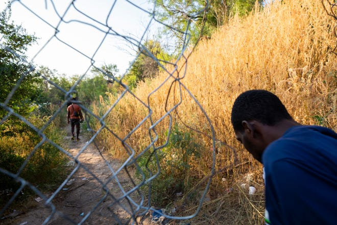 Haitian migrants walk back from Del Rio, Texas to Ciudad Acuna to get food and water.