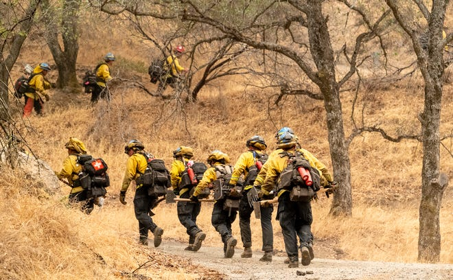 Firefighters head off Friday, September 17, 2021 to clear a defensible space around homes in Three Rivers along Highway 198 as the KNP Complex Fire continues to burn in Sequoia National Park.