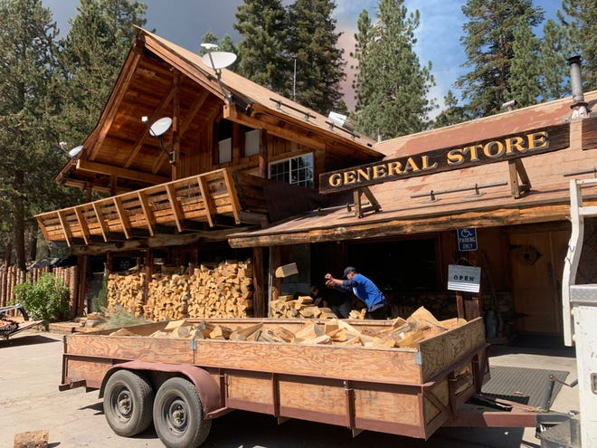 Employees at the Ponderosa Lodge load up a hauler with the winter's firewood as the Windy Fire climbs up Slate Mountain just west of the town.