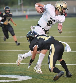 Henrietta Bearcats quarterback Braden Bell (3) spins out of a tackle by Archer City defensive back McKinnen Beaver (1) Friday night in Archer City.