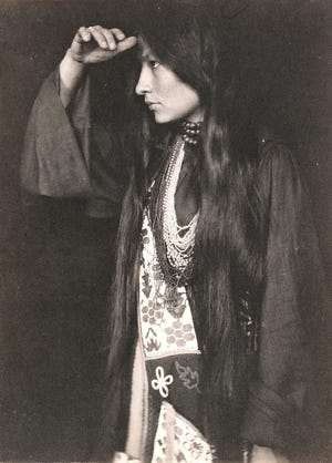 """Lakota author and activist Zitkála-Šá pictured in 1898. As a girl, she was forcibly sheared. As an adult, she wrote of the experience: """"I cried aloud, shaking my head all the while until I felt the cold blades of the scissors against my neck, and heard them gnaw off one of my thick braids. Then I lost my spirit...now I was only one of many little animals driven by a herder."""""""
