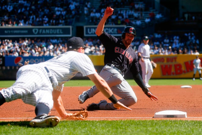 Cleveland's Bradley Zimmer, right, dives safely into third base as New York Yankees' DJ LeMahieu tries to tag him out in the first inning of a baseball game, Sunday, Sept. 19, 2021, in New York. (AP Photo/Eduardo Munoz Alvarez)