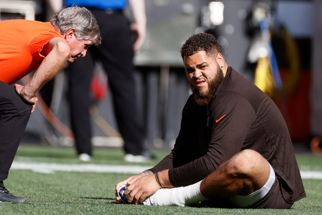 Browns offensive tackle Jedrick Wills stretches under watch from offensive lines coach Bill Callahan before a game against the Houston Texans, Sunday, Sept. 19, 2021, in Cleveland. (AP Photo/Ron Schwane)
