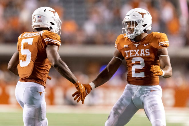 Texas running backs Bijan Robinson, left, and Roschon Johnson celebrate Robinson's touchdown run in the first half of the Longhorns' 58-0 win over Rice. Robinson scored three touchdowns on the night.