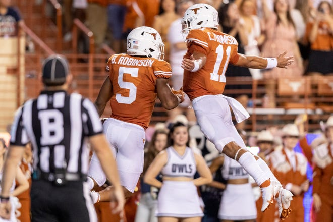 Texas running back Bijan Robinson, left, celebrates a first-half touchdown run with Longhorns quarterback Casey Thompson during Saturday night's 58-0 win over Rice at Royal-Memorial Stadium. The Longhorns improved to 2-1.