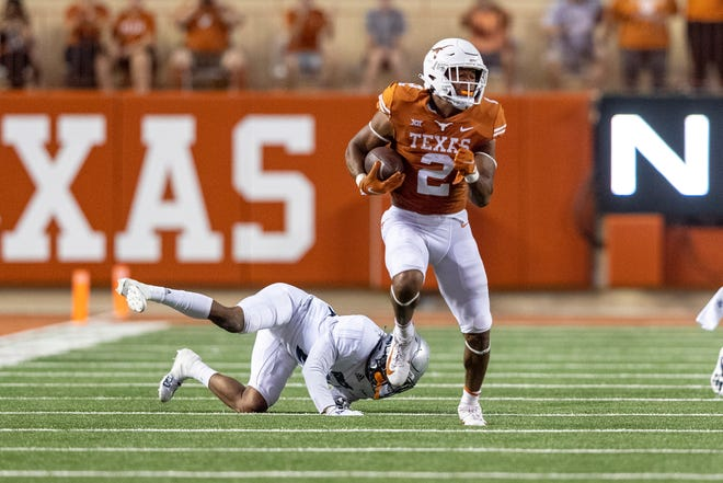 Texas running back Roschon Johnson breaks a tackle attempted by Rice cornerback Miles McCord during a 72-yard touchdown run in the Longhorns' 58-0 win over the Owls on Saturday at Royal-Memorial Stadium. Johnson finished with 112 yards on just three carries.